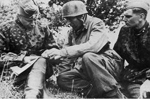 Major von der Heydte (center), commanding FJR 6, informs Brigadeführer Werner Ostendorf, head of the 17th SS-Panzer Division, of the situation at Carentan. Ostendorf was critical of Heydte's defense of the city, despite the paratroopers' being given little ammunition or support.