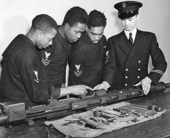 Three of the Mason's gunner's mates are instructed at the Norfolk Naval Training Station, Virginia, in the assembly of a 20mm machine gun—the type they will man aboard the ship. Photo taken January 3, 1944.