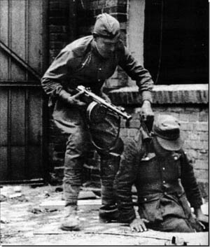A Soviet soldier, armed with a PPSh-41 submachine gun, drags a German defender from his hiding place.