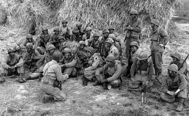 After battling for weeks on the Winter Line, the 1st SSF was moved to bolster the Anzio beachhead. A night patrol, with soldiers' faces blackened, is being briefed behind an Italian haystack before moving out, April 20, 1944.