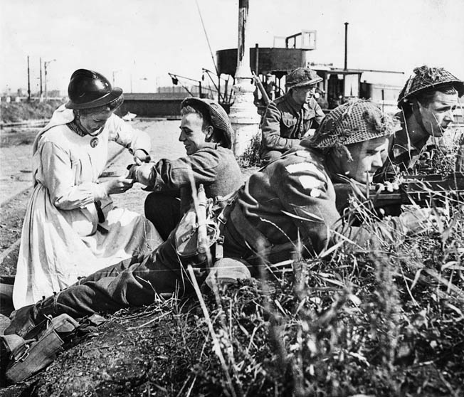 British commandos are on the alert as a slightly wounded soldier is treated by a Belgian Army nurse during the British seizure of Antwerp, September 4, 1944. The port of Antwerp could not be used until Walcheren Island and the Lower Scheldt Estuary were in Allied hands.