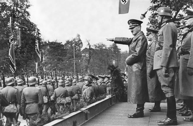 Within weeks of their invasion of Poland from the west, German troops occupied the Polish capital of Warsaw. In this photo, Hitler watches Wehrmacht soldiers pass in review. The parade took place in Warsaw about a month after the outbreak of World War II, and at the time the photo was taken, Soviet troops had invaded Poland from the east.