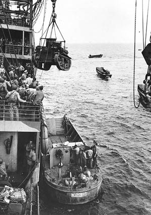 A U.S. Marine Corps M2A4 Stuart light tank is hoisted from the attack cargo ship USS Alchiba (AK-23) into a LCM(2) landing craft off the Guadalcanal invasion beaches on the first day of the landings, August 7, 1942.