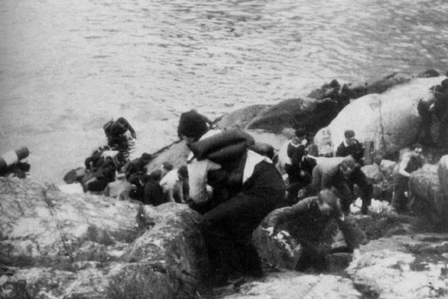 Stunned that their warship has been vanquished by Norwegian shore batteries, sailors from the German cruiser Blücher reach temporary safety on the rocky shoreline.