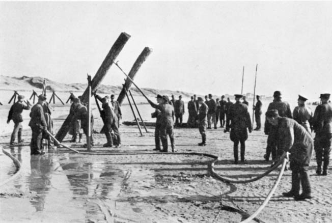 With Field Marshal Rommel (far right) looking on, German troops install antilanding-craft obstacles on a Normandy beach. Many of the obstacles were fitted with mines designed to explode on contact.