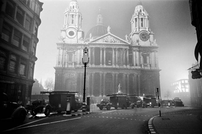 Illuminated solely by fires burning around it, St. Paul's stands tall. A bomb landed on its main steps but failed to explode, another lodged in the dome.