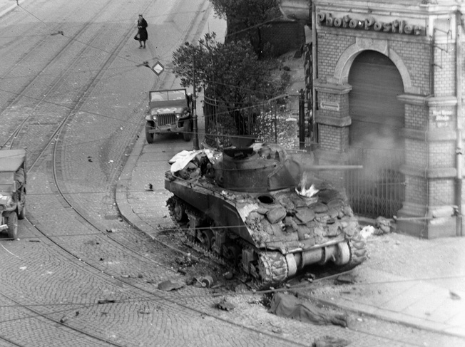 An abandoned American Sherman tank, destroyed by a direct hit from a German Faustpatrone, hollow-charge projectile, sits on a street in Leipzig, Germany. BELOW: Some M4 tanks were equipped with 4.5-inch rocket launchers and dubbed Calliopes. Although the rockets were inaccurate, they could saturate a significant area with high-explosive ordnance.