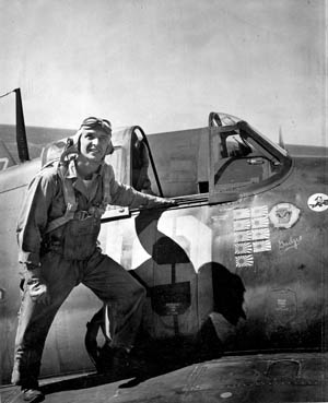 U.S. Navy fighter ace Alex Vraciu stands next to the cockpit of his Grumman F6F Hellcat fighter plane prior to a mission. On the Hellcat's fuselage are rising sun emblems representing nine confirmed aerial kills. Vraciu finished the war with 19 victories.
