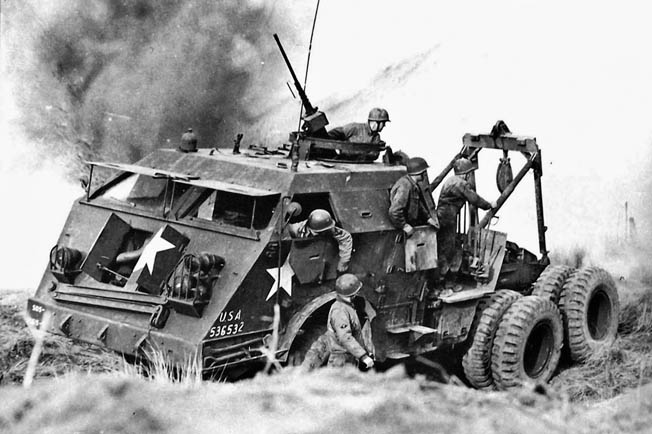 During a training exercise in England with simulated explosions providing an air of realism, an M26 truck powered by a Hall-Scott engine pulls a tank out of a crater.