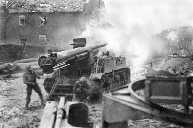 American artillerymen fire a powerful M-12 155mm self-propelled gun at a target in the streets of Aachen in October 1944. These weapons were employed to blast stubborn German bunkers when tank fire proved ineffective.