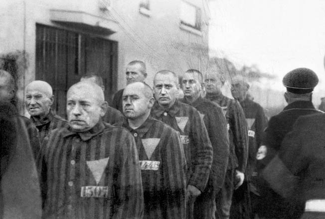 Standing mutely at attention in bitterly cold weather, prisoners at the Sachsenhausen concentration camp are under the watchful eyes of Nazi guards. This photo was taken on December 19, 1938.