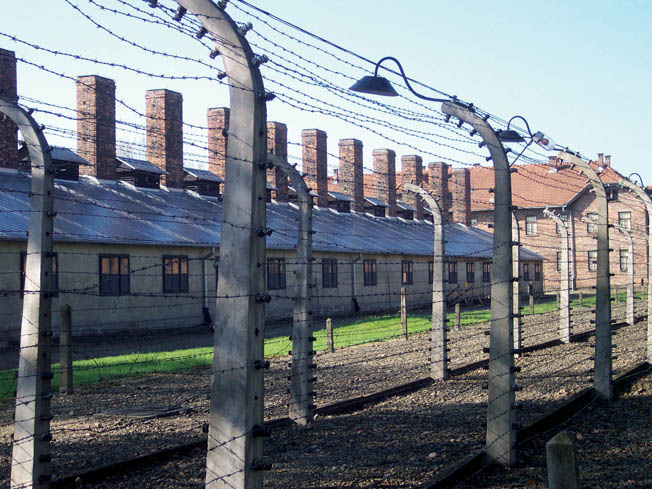 Barbed wire fencing remains in place around the perimeter of the Nazi death camp at Auschwitz. Located in Poland, Auschwitz was the scene of mass extermination on a colossal scale.