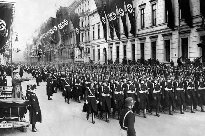 Hitler (far left, in car) salutes his bodyguard unit, the 1st SS Division Leibstandarte Adolf Hitler (LAH), during a January 1937 parade in Berlin.