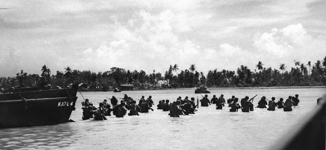 American soldiers of the 27th Infantry Division wade ashore on Makin atoll in the Gilbert Islands on November 20, 1943, while a tank makes its way along the beach in the distance.
