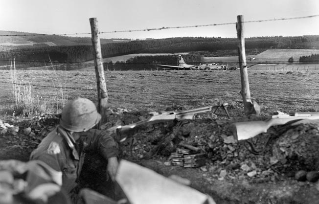 Emil Edgren shot this image of an American GI with a Browning Automatic Rifle looking at a B-17 that crash-landed in a Belgian field.
