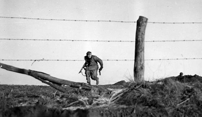 A helmetless American paratrooper from the 82nd Airborne Division carrying a tommygun in full gallop across a Belgian field was captured by the lens of Emil Edgren