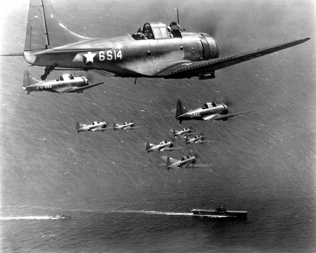 Flying in formation, a squad of Dauntless dive-bombers from Scout Squadron Six return to the USS Enterprise.