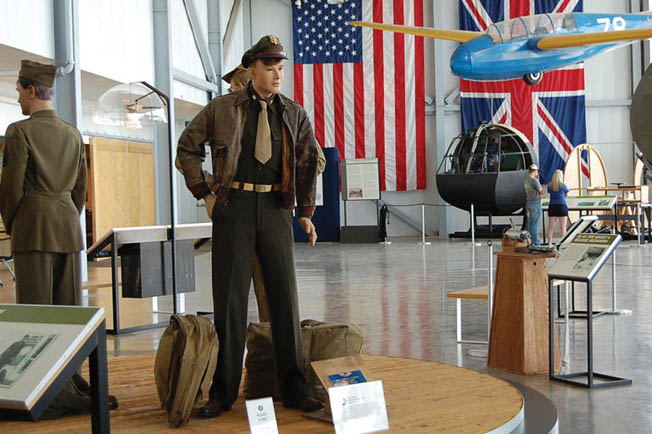 World War II uniforms on display along with a Laister-Kauffman TG-4 training glider and nose section of a British Horsa glider in the background.