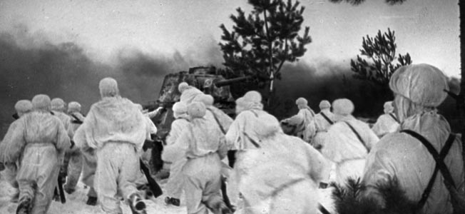 Cloaked in white camouflage and uniformed against the extremely cold weather, Red Army infantrymen hurry toward one of their own tanks while others climb aboard to hitch a ride rather than trudge through the deep snow.
