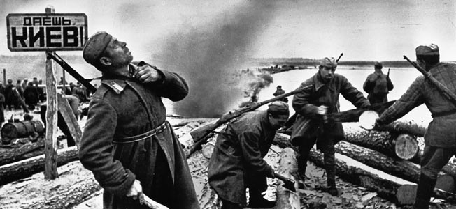During the fighting around the Ukrainian capital of Kiev, Soviet sappers establish a crossing of the Dnepr River. One of the sappers is looking skyward in response to noise from approaching aircraft.