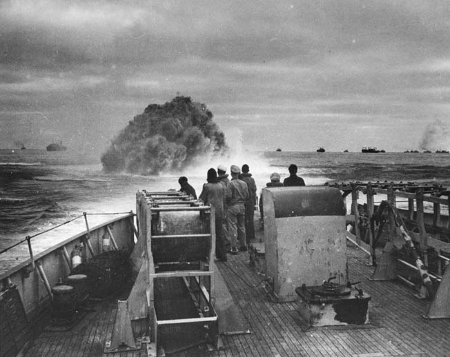 Crewmen aboard the U.S. Coast Guard Cutter Spencer watch the waters of the Atlantic Ocean brew up with the detonation of a depth charge. This photograph was taken while the Spencer was defending a trans-Atlantic convoy, visible in the background, against a German U-boat attack.