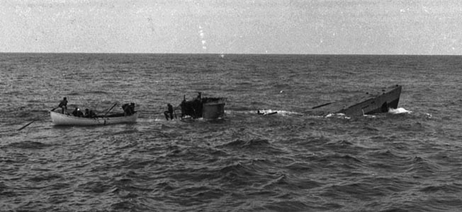 After their U-boat quarry has sustained damage from an effective depth charge attack and risen to the surface, crewmen of the Spencer pick up survivors before the stricken submarine plunges to the bottom of the Atlantic.