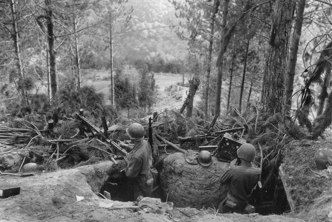 GIs clear and inspect a German machine-gun nest in the Hürtgen Forest after a firefight. Felled trees and evergreen branches augmented the strength of the position.