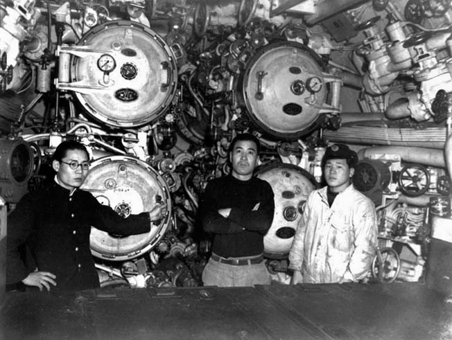 Three former crew members of I-58 pose next to the submarine's torpedo tubes, which loosed lethal Long Lance torpedoes and sank the Indianapolis during the last days of World War II.