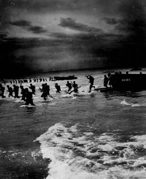 Landing craft unload their cargoes of U.S. Army troops on the beach in North Africa during the opening hours of Operation Torch on November 8, 1942. These troops are coming ashore south of Port Lyautey, where heavy surf played havoc with the initial landings, damaging numerous landing craft and disrupting the timetable for the movement inland toward the earliest Torch objectives.