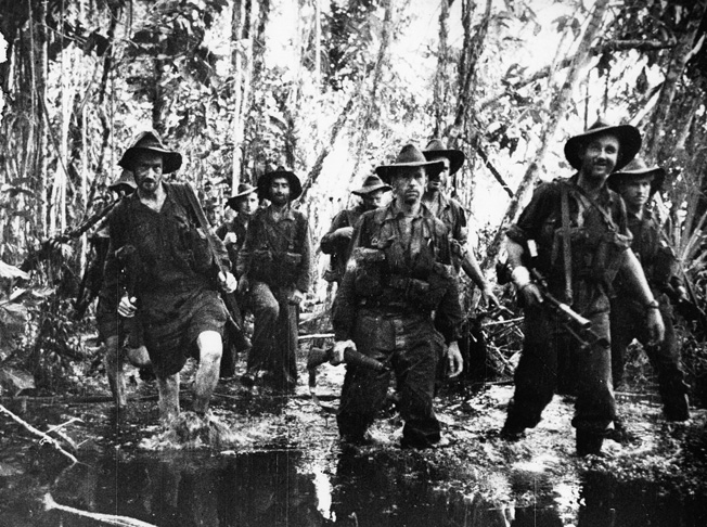 Australian troops slosh through knee-deep water in the jungles of Buna. The stifling heat and swampy, insect-infested terrain took a harsh toll on the morale of many.