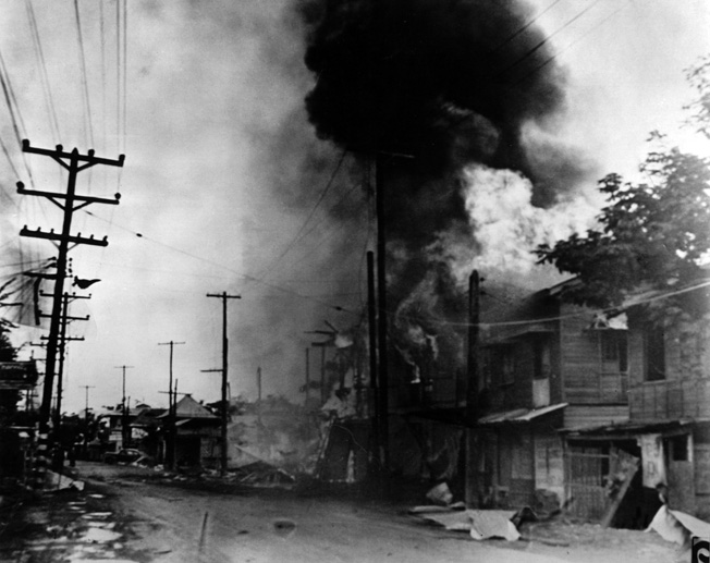 Charred and burning buildings line the streets in Manila shortly after a Japanese bombing raid.