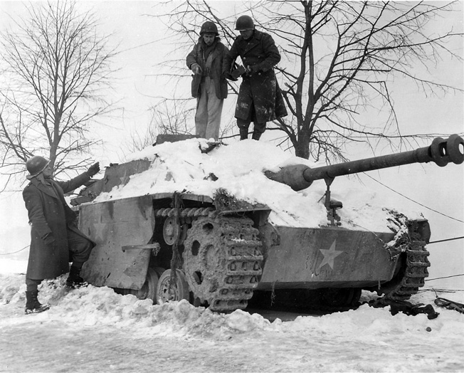 Combat engineers attempt to remove an abandoned German tank. Disguised with U.S. markings, this vehicle was probably used in the attack on Malmedy.