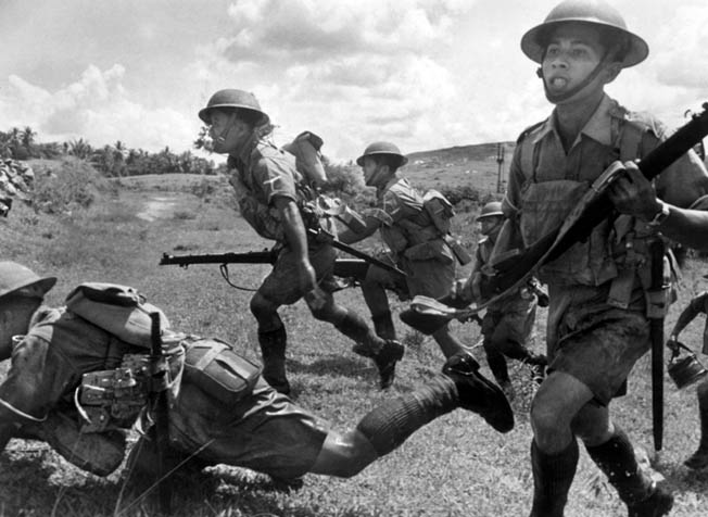 Malay soldiers, equipped with British uniforms and weapons, take part in exercises in typical Malayan swamp country.
