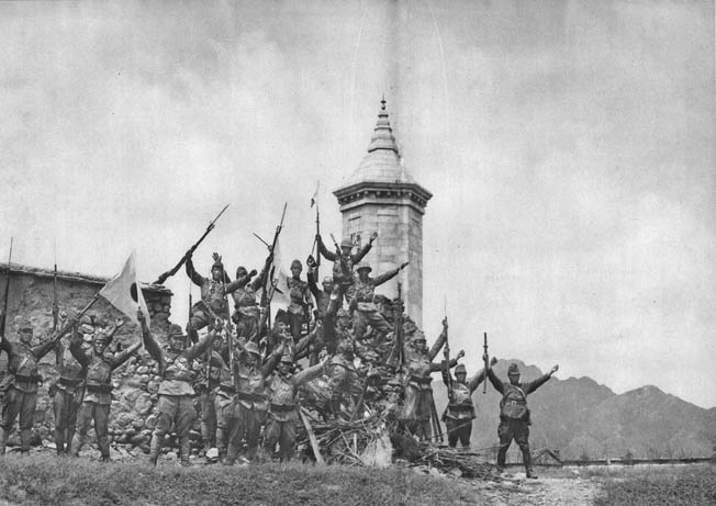 Japanese soldiers stand atop the ruins of a brick wall and deliver a rousing banzai cheer after the capture of Beijing. The city fell at the end of July 1937, and the Japanese invaders were emboldened to seek new conquests on the Asian mainland.