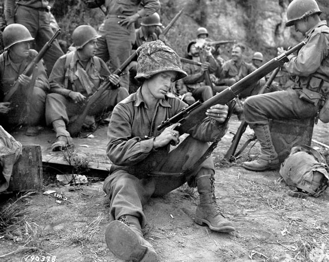 During a pause in the action near the town of Valletri, Italy, on May 29, 1944, Pfc. Edward J. Foley of the 143rd Infantry Regiment, 36th Division, cleans his Springfield M1903A4 sniper rifle. The remarkable service life of the M1903 rifle extended through the Vietnam era and beyond.