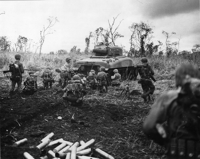 With armor leading the way, U.S> Marines advance on a Japanese pillbox. Often, such enemy strongpoints had to be reduced by individual soldiers with satchel charges or point-blank fire from armored vehicles.