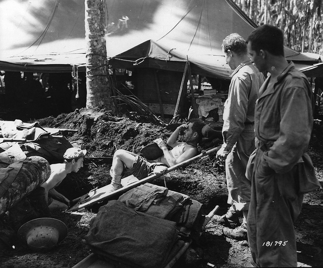 Wounded in action during Operation Cartwheel, a soldier of the 43rd Infantry Division is moved on a stretcher to the operating room at the division's field hospital. The advent of the field hospital in World War II saved the lives of many wounded Americans.