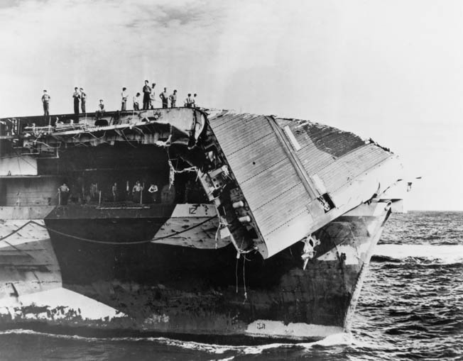 Sailors inspect the damage to the flight deck of the aircraft carrier USS Hornet after Typhoon Connie subsided.